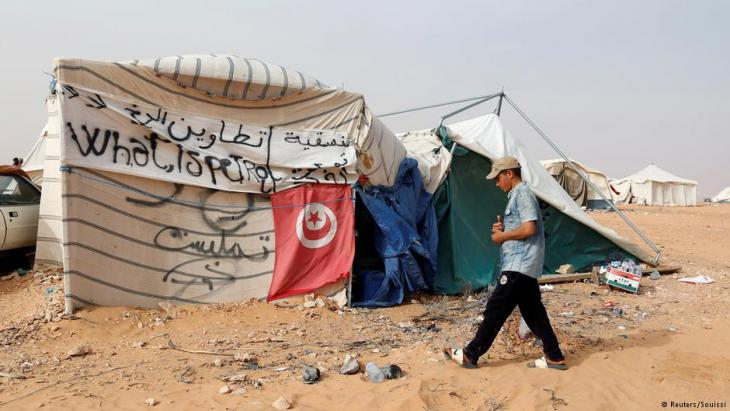 A Tunisian protester walks near his tent during the sit-in at El Kamour oilfield, demanding jobs and a share in revenue from the area's natural resources near the town of Tatouine, Tunisia May 11 2017 (photo: Reuters/Zoubeir Souissi)