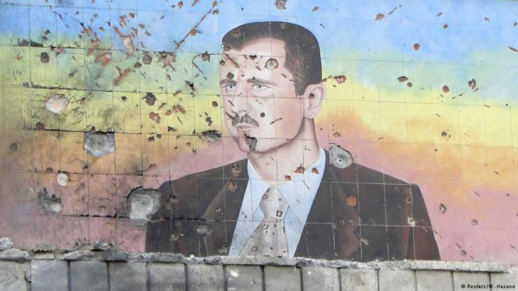 Shrapnel-scarred and pockmarked facade of a police building in Aleppo bearing a likeness of Assad (photo: Reuters)