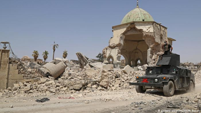 An armoured vehicle drives past a destroyed building in Mosul (photo: picture-alliance/AA/H. Baban)