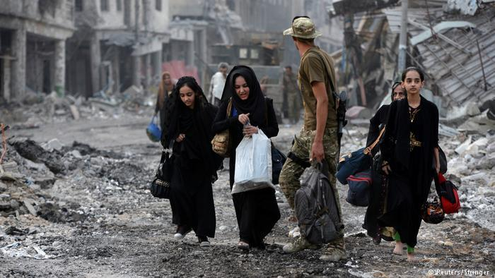 People walk through a destroyed neighbourhood of Mosul (photo: Reuters/Stringer)