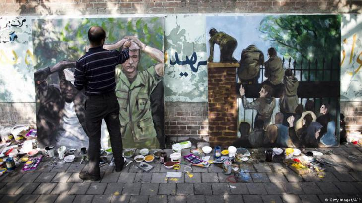 Iranian man puts the final touches to his painting outside the former U.S. embassy in Tehran, depicting the U.S. hostages following the storming of the embassy compound by Islamist students in 1979 (photo: Behrouz Mehri/AFP/Getty Images)