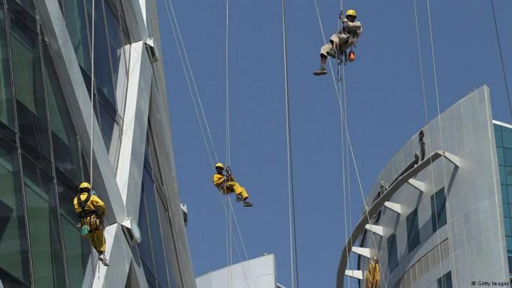 Nepalese window cleaners abseil down the facade of Tornado Tower (left) in Doha, Qatar (photo: Getty Images)