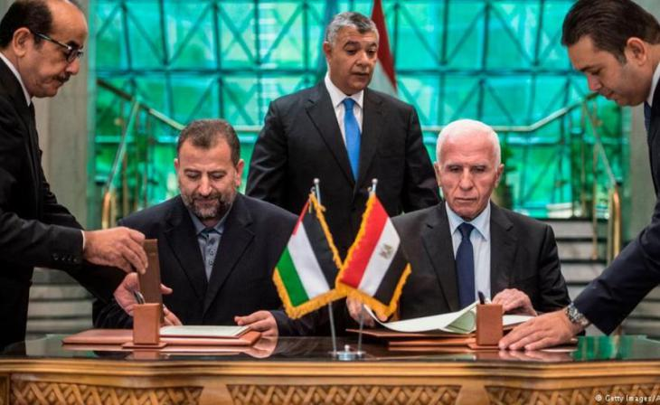 Hamas representative Saleh al-Arouri and Fatah's negotiator Azzam al-Ahmed sign the reconciliation agreement in Cairo under the watchful eye of Khaled Fawzy, the head of Egypt′s General Intelligence Directorate (photo: Getty Images/AFP/K. Desouki)