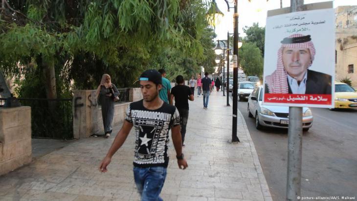 People walk past election posters on a street in Amman, Jordan, on 06.07.2017 (photo: AP Photo/S. Malkawi)