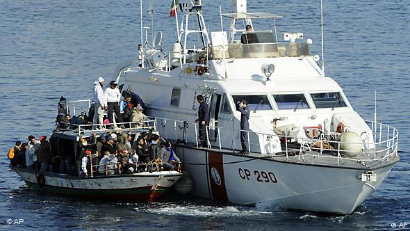An overcrowded boat full of migrants alongside a boat belonging to the Italian coast-guard (photo: AP)
