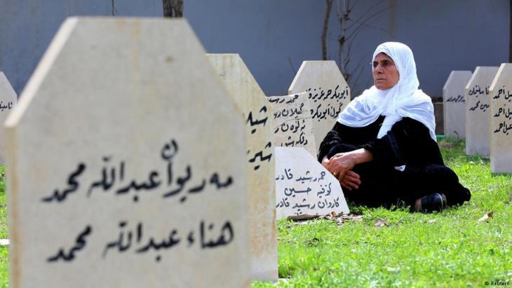 A woman sits among the graves of victims of the Halabja chemical attack (photo: Reuters)