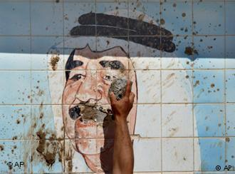 A Kurd destroys a tiled image of Saddam Hussein in northern Iraq following his overthrow in 2003 (photo: AP)