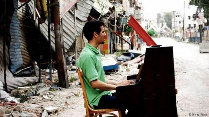 Aeham Ahmad playing his piano among the rubble, Syria (photo: Niraz Saied)