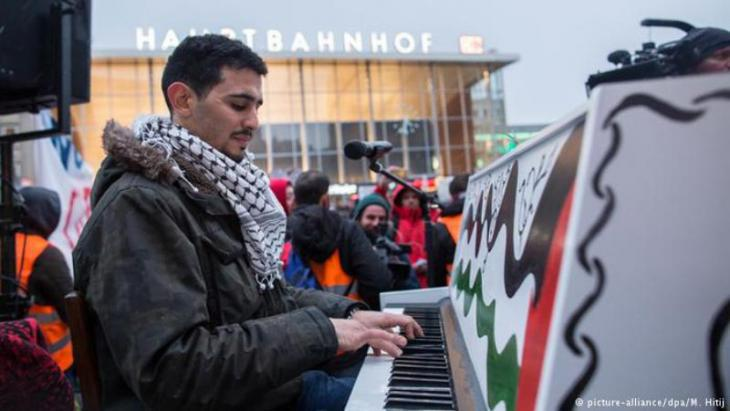 Aeham Ahmad playing his piano outside Cologne Central Station (photo: picture-alliance/dpa/M. Hitij)