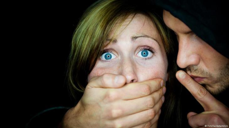 Symbolic image of violence against women and honour killings showing a man with his hand around a woman′s mouth (photo: Fotolia/detailblick)