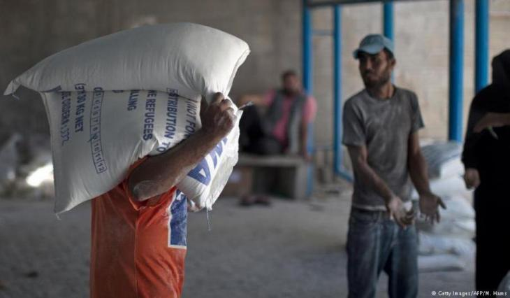 Palestinian carries sacks of flour at a United Nations Relief and Works Agency distribution centre in Gaza City, 17.09.2013 (photo: Getty Images/AFP/M. Hams)