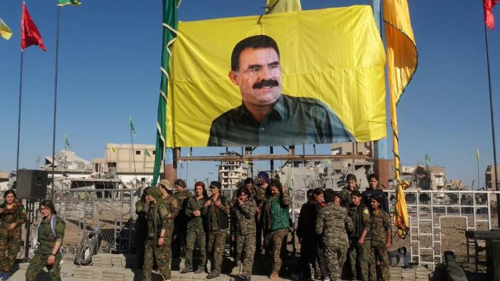 Syrian Democratic Forces units gather below a banner of PKK leader Ocalan following the fall of Raqqa on 19 October 2017 (photo: AFP/Getty Images)