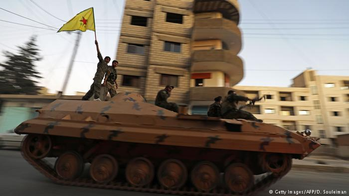 YPG fighters ride on a tank through the town of Qamishli in northeastern Syria, close to the Turkish border (photo: AFP/Getty Images)