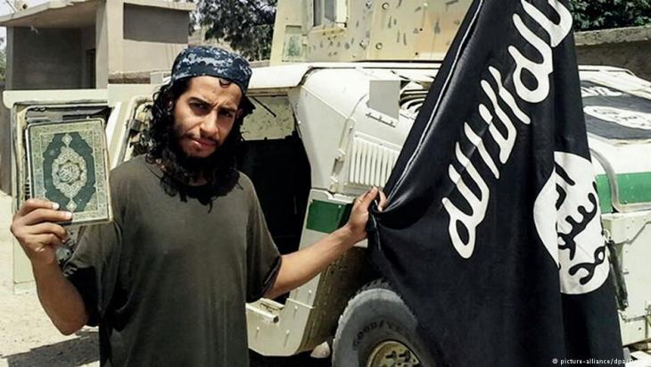 IS terrorist Abdelhamid Abaaoud with the IS flag and Koran (photo: picture-alliance/dpa)