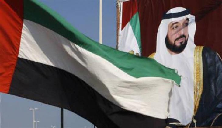 United Arab Emiratesʹ flag and a billboard showing Sheikh Khalifa bin Zayed Al-Nahyan in Abu Dhabi (photo: Reuters/Ahmed Jadallah)