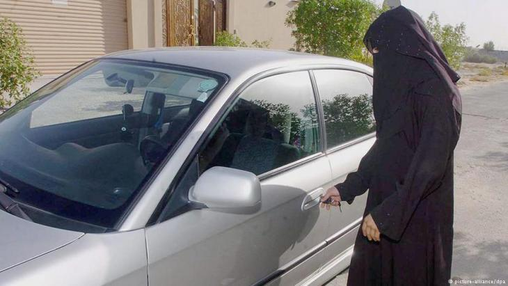 Saudi woman opens the door to her family car in Riyadh (photo: picture-alliance/dpa)