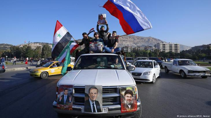 Assad supporters wave Syrian, Russian and Iranian flags in Damascus (photo: picture-alliance/AP)