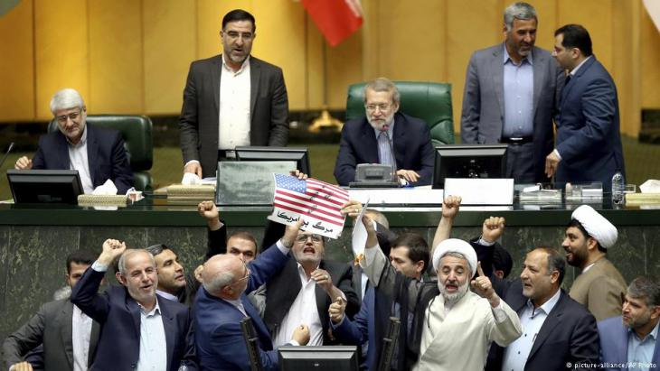 Iranian lawmakers burn pieces of papers representing the U.S. flag and the nuclear deal as they chant slogans against the U.S. at the parliament in Tehran on 9 May 2018 (AP Photo)