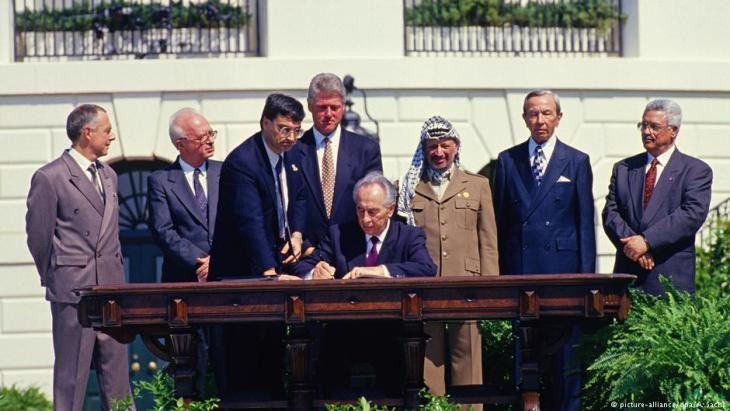 Minister of Foreign Affairs of Israel Shimon Peres puts his signature on the agreement during the signing ceremony of the historic Israeli-PLO Agreement, known as the Oslo 1 Accord, on the South Lawn of the White House in Washington, DC on September 13, 1993. Pictured, from left to right: Foreign Minister Andrei Kozyrev of Russia; Prime Minister Yitzhak Rabin of Israel; unknown aide; United States President Bill Clinton; Peres; Chairman Yasser Arafat of the Palestine Liberation Organisation (PLO); U.S. Secretary of State Warren Christopher; and Arafat aide Mahmoud Abbas (photo: picture-alliance/dpa/A. Sachs)