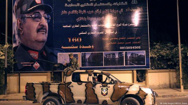 Army vehicle in front of a billboard depicting General Khalifa Haftar in Benghazi (photo: Getty Images/AFP)