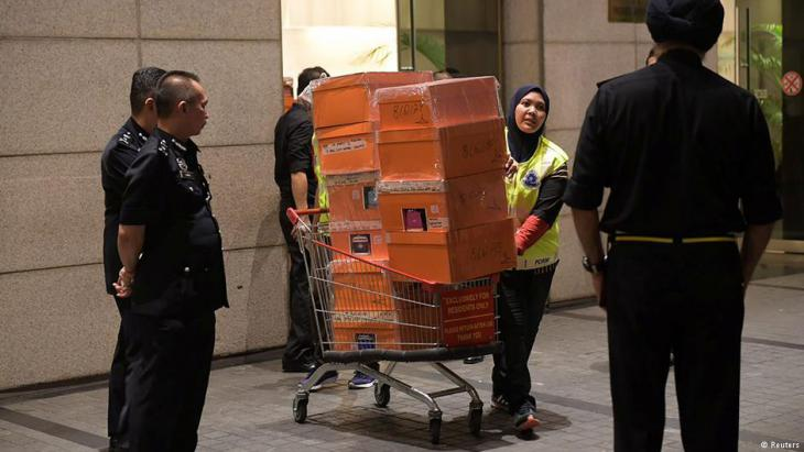 A Malaysian police officer pushes a trolley during a raid of three apartments in a condominium owned by former Malaysian prime minister Najib Razak's family, in Kuala Lumpur, on 17 May 2018, in this photo taken by The Straits Times (source: Reuters)