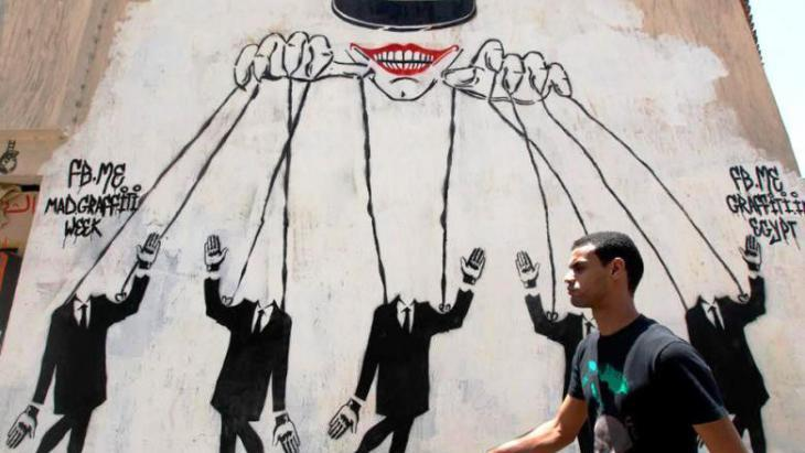 Graffiti in Cairo showing the military as puppet master (photo: Nasser Nasser/AP)