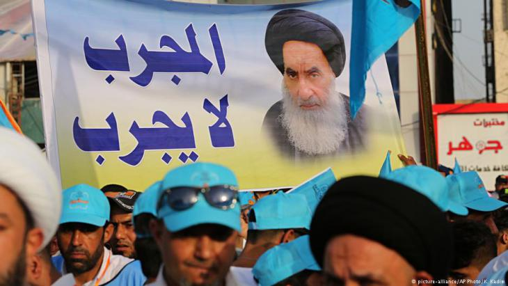 Followers of Shia cleric Muqtada al-Sadr hold a poster of Shia spiritual leader Grand Ayatollah Ali al-Sistani during a parliamentary campaign rally in Baghdad, Iraq, 4 May 2018 (photo: picture-alliance/AP Photo/K. Kadim)