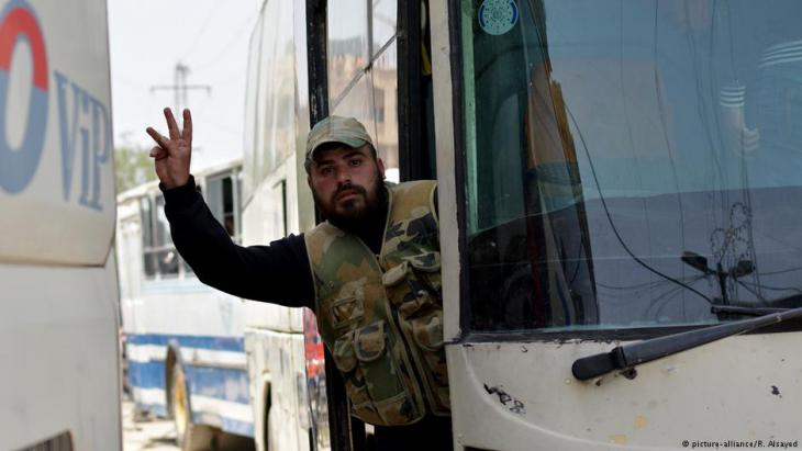 A man gestures from a bus of the first convoy carrying members of the Free Syrian Army (FSA) and civilians as the convoy departs from the FSA-controlled area of Yarmouk Camp in southern Damascus under the Yarmouk camp evacuation agreement, as part of the compulsory evacuation, on 3 May 2018 (photo: picture-alliance/R. Alsayed)
