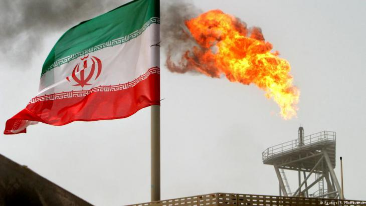 A gas flare on an oil production platform in the Soroush oil fields is seen alongside an Iranian flag (photo: Reuters/R. Homavandi)