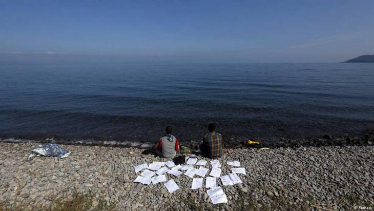 Two Syrian refugee students dry their documents on a beach on the Greek island of Lesbos, 19 October 2015 (photo: Reuters/Yannis Behrakis)