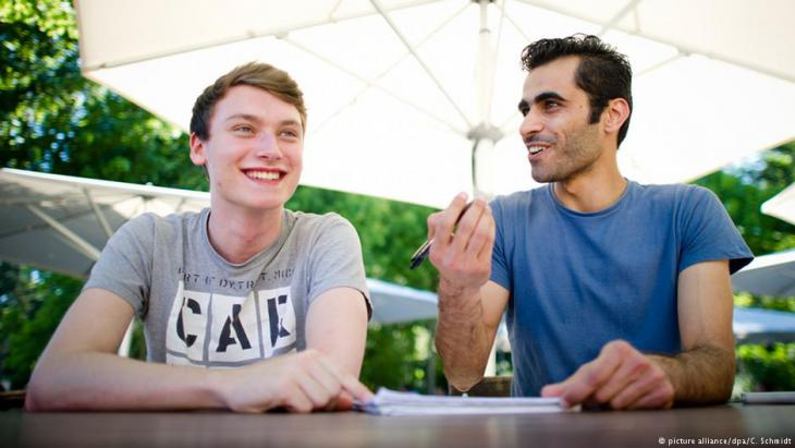 Student Tim Schwarz (left) gives Syrian refugee Renas Ottmann (right) German tuition in the grounds of the Goethe University in Frankfurt am Main on 30.06.2015 (photo: picture alliance/dpa/C. Schmidt)