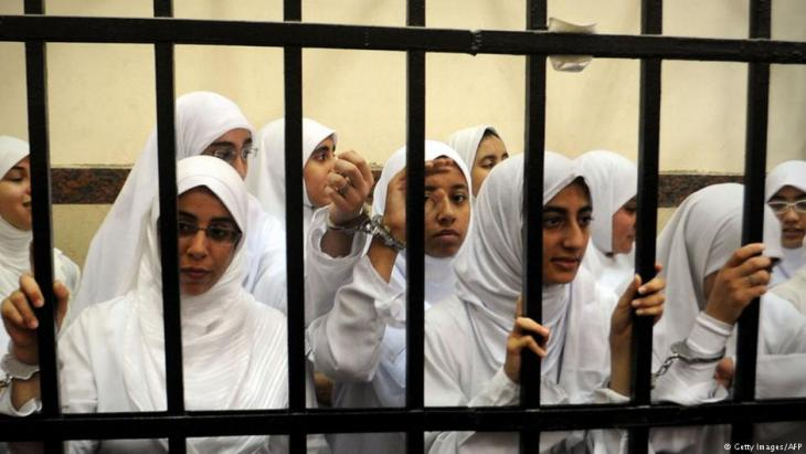 Female members of the Muslim Brotherhood are seen during their trial in the Egyptian city of Alexandria on 27 November 2013. A court in the Mediterranean city sentenced 14 women whom it said were from the Brotherhood after convicting them of belonging to a 'terrorist organisation,' judicial sources said (photo: Getty Images/AFP)