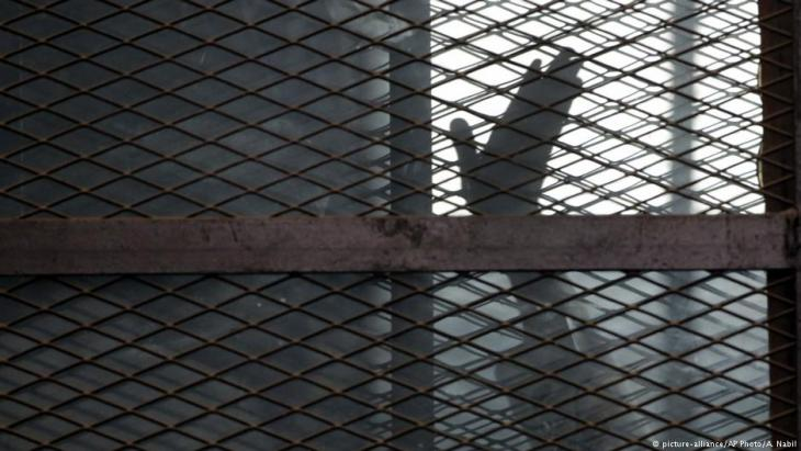 A Muslim Brotherhood member gestures from a defendantsʹ cage in a courtroom in Torah prison, southern Cairo, Egypt 22 August 2015 (photo: picture-alliance/AP Photo/A. Nabil)