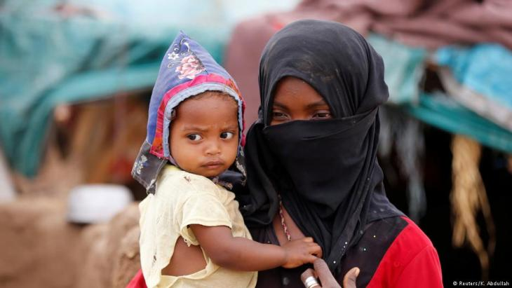 A girl carries a child near a hut in an improvised camp for internally displaced people near Abs of the northwestern province of Hajja, Yemen, 18 February 2019 (Reuters/K. Abdullah)