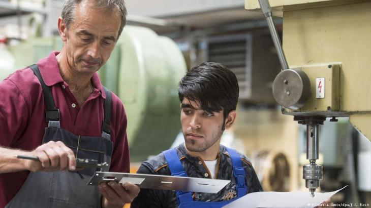 Trainer Wolfgang Wonneberger (l) from Jenaer Feinblech GmbH in Jena, Thuringia demonstrates working techniques to 19-year-old Afghan refugee Rezwan Waziri, 25.08.2016 (photo: picture-alliance/dpa/J.-U. Koch)