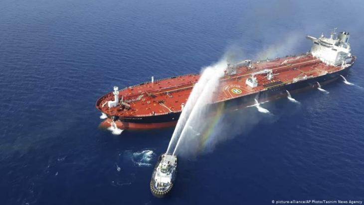 An Iranian navy boat sprays water to extinguish a fire on an oil tanker in the sea of Oman, 13 June 2019 (photo: picture-alliance/AP Photo/Tasnim News Agency)