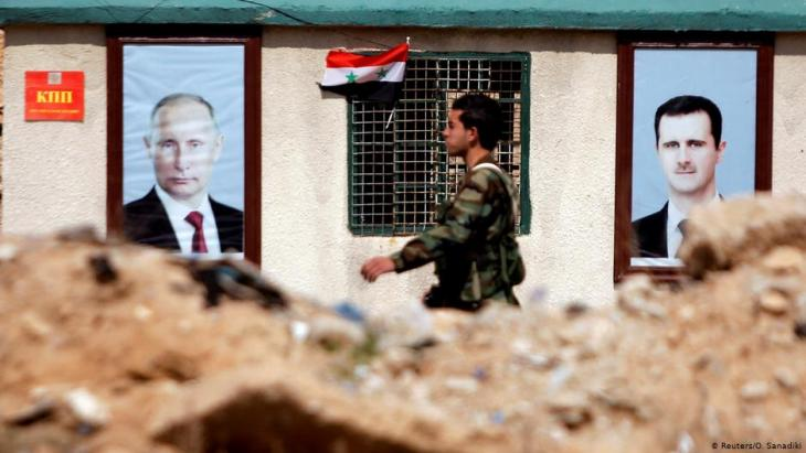 Syrian soldier walks past portraits of Putin and Assad in Eastern Ghouta near Damascus (photo: Reuters/Omar Sanadiki)