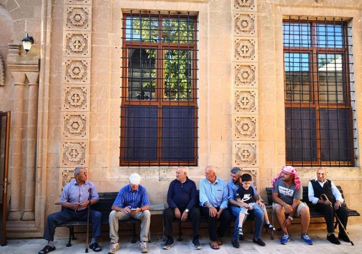 People sit in the shade in front of the Mor Barsamo Church in Midyat (photo: Marian Brehmer)
