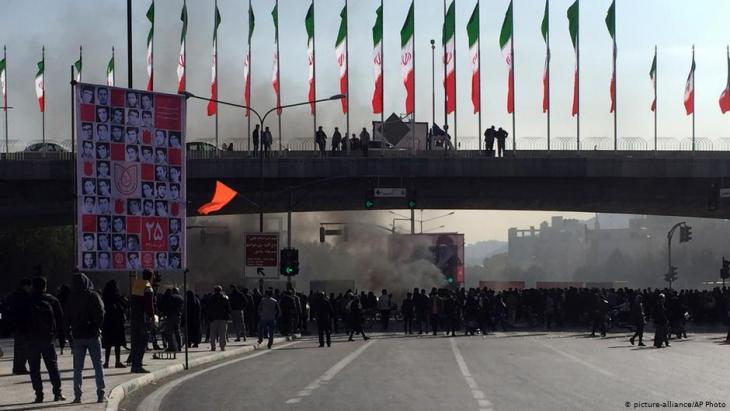 Smoke rises during protests against a rise in petrol prices in Isfahan, Iran (photo: picture-alliance/AP Photos)