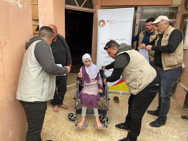 Amal sits in her new wheelchair, to her right stands Faris the construction engineer (photo: RIRP)