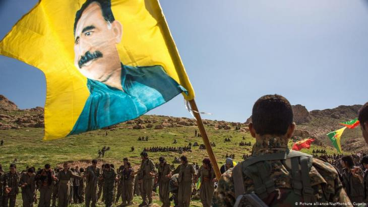 Kurdish militias carry a flag of PKK founder Abdullah Ocalan (photo: picture-alliance/NurPhoto/D. Cupolo)