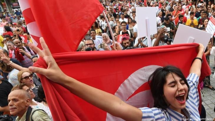 Tunisian women chant slogans as they wave national flags during a demonstration to mark Tunisia's Women's Day and to demand equal inheritance rights between men and women in Tunis on 13 August 2018 (photo: AFP/Getty Images/Fethi Belaid)