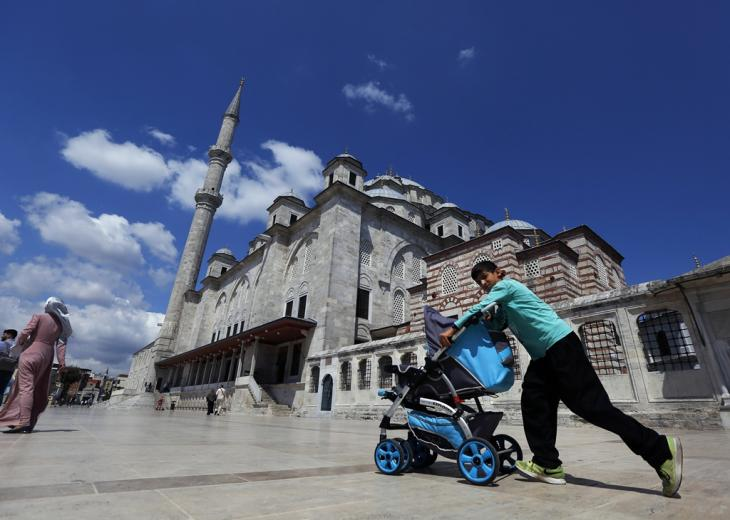 A Syrian boy pushes a pram past Fatih mosque in Istanbul, August 2019 (photo: picture alliance/AP Photo/Lefteris Pitarakis)