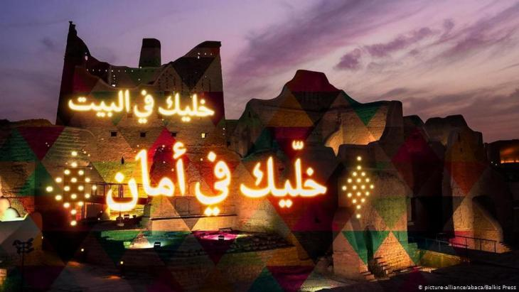 Message asking Saudis to stay home and thanking the leadership and King Salman, and Crown Prince Mohammed bin Salman, being shown on the ancient Salwa Palace, during lockdown to fight COVID-19, in Diriy, Saudi Arabia (photo: picture-alliance/abaca/Balkis Press)