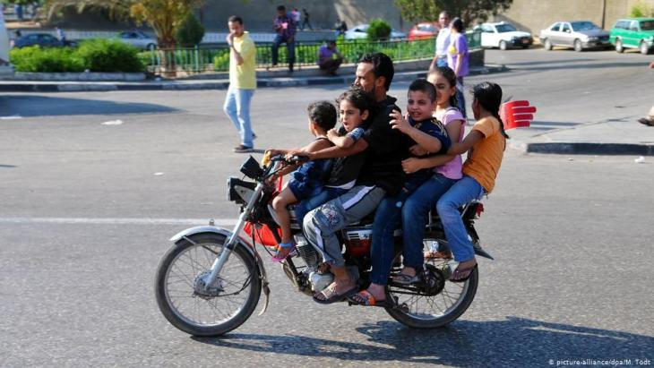A father driving his five children on a motorbike to Tahrir Square in Cairo (photo: dpa/picture-alliance)
