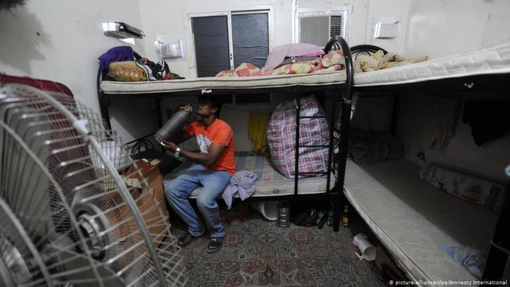 A migrant worker sits on his bunk in shared accommodation in Qatar (photo: dpa)