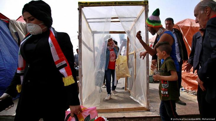Demonstrators on Tahrir Square in Baghdad pass through a makeshift disinfection tunnel erected by the protest movement to help prevent the spread of the novel coronavirus (photo: picture-alliance/dp/AP/K. Mohammed)