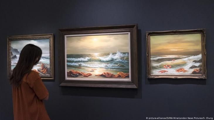 "Woman looks at the ""Mediterranean Sea View 2017""  by the artist Banksy (photo: picture-alliance/ZUMA Wire/London News Pictures/S. Chung)"