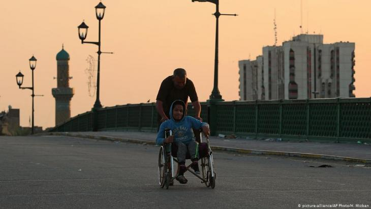 One man pushes another in a wheelchair down a street in Iraq (photo: picture-alliance/AP Photo/H. Mizban)
