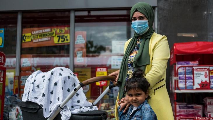 A woman in a headscarf and medical face mask pushes a pushchair holding her daughter's hand (photo: Sanne Derks)